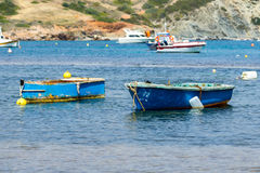 Small fishing boats off the coast in one of the bays. Stock Images