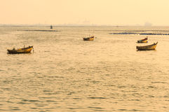 Small fishing boats on the sea during sunset Royalty Free Stock Image
