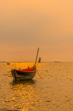 Small fishing boats on the sea during sunset and clouds Stock Photos