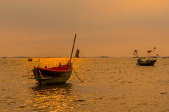 Small fishing boats on the sea during sunset and clouds. Royalty Free Stock Image