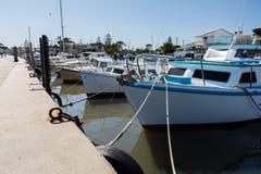 Small fishing boats tied to wharf stock photos