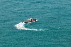 Small fishing motorboat boat turns. In Busan port area at sunny day, South Korea royalty free stock images