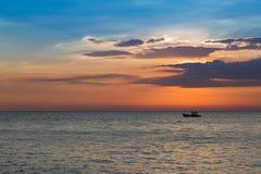 Small fishing ship over sunset seacoast skyline Royalty Free Stock Photo
