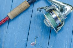 Small fishing spoon, fishing reel, spinning for pike, bass, predator fishing. Fishing set Royalty Free Stock Photo