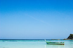 Small fishing wooden boat in blue sea and sky Royalty Free Stock Photography