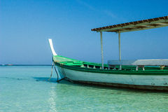 Small fishing wooden boat in blue sea and sky Stock Images