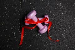Small fitness dumbbells on a black background of the floor royalty free stock photo