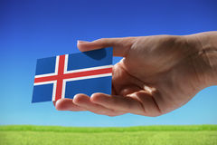 Small flag of Iceland. Against beautiful landscape with grass Royalty Free Stock Image