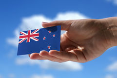 Small flag of New Zeland. Cumulus clouds in background Stock Images