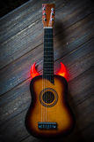 Small flamenco guitar. With red horns or flames on wooden tabletop Royalty Free Stock Photography