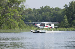Small floatplane lands on a Minnesota lake. A small white floatplane lands on a Minnesota lake in summer Stock Photos