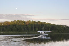 Small floatplane taxis for takeoff on calm Minnesota lake. A small floatplane taxis for takeoff on a calm Minnesota lake at sundown Stock Photos