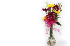 Small Flower Bouquet. A small bouquet of yellow and purple daisies in a glass vase with a purple bow Royalty Free Stock Photography