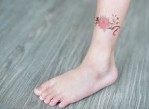 Small flower tattoo sticker on child ankle, Dress up tattoo.  stock photography