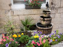 Small flowerbed in front of a window with a fountain royalty free stock photo