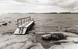 Small foot bridge over rocks into the sea. Small wooden foot bridge over rocks leads into the sea Stock Image