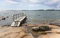 Small foot bridge over rocks into the sea. Small wooden foot bridge over rocks leads into the sea Royalty Free Stock Image