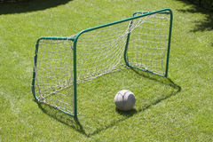 Small football gate with net and ball on the play-field as a back Royalty Free Stock Images