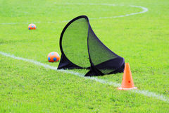 Small football gate for training kids to sports football, balls and plastic limiter in a stadium with green lawn grass Stock Image