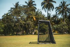 Small football or soccer gates and the pitch. Outdoor side view of a small football or soccer gates for children and part of the field, with the palm trees and Stock Images