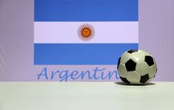 Small football on the white floor and Argentinean nation flag with the text of Argentina background. stock images