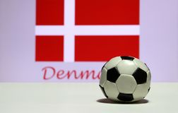 Small football on the white floor and out focus white cross on red of Danish nation flag background with Denmark text. Royalty Free Stock Image
