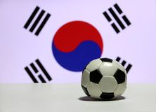 Small football on the white floor with out focus red and blue Yin Yang and four black trigrams of South Korean nation flag. Small football on the white floor stock photo