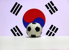 Small football on the white floor with red and blue Yin Yang and four black trigrams of South Korean nation flag background. The concept of sport stock image