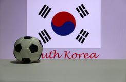 Small football on the white floor and South Korean nation flag with the text of South Korea background. The concept of sport royalty free stock photo