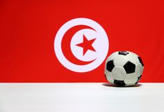 Small football on the white floor and Tunisian nation flag with moon and star background. The concept of sport royalty free stock photography