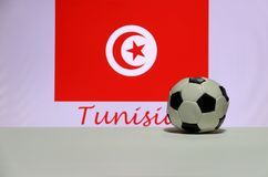 Small football on the white floor and Tunisian nation flag with the text of Tunisia background. The concept of sport royalty free stock photos