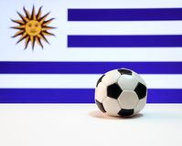 Small football on the white floor and Uruguayan nation flag background. The concept of sport Royalty Free Stock Photo