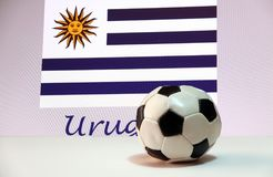 Small football on the white floor and Uruguayan nation flag with the text of Uruguay background. The concept of sport Royalty Free Stock Photo