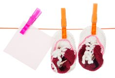 Small footwear dries on a rope with clothespegs Stock Images