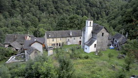 Small forgotten traditional village and church, lost on the Italian Swiss Alps near Locarno Royalty Free Stock Photo