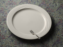 Small fork on empty dinner plate Stock Image