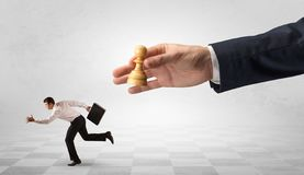 Small businessman running away from big hand with chessman concept. Small frail businessman with suitcase running away from big hand with chessman conceptn royalty free stock photo