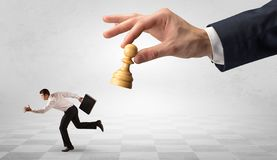 Small businessman running away from big hand with chessman concept stock illustration