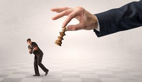 Small businessman running away from big hand with chessman concept. Small frail businessman with suitcase running away from big hand with chessman concept stock image