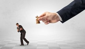 Small businessman running away from big hand with chessman concept. Small frail businessman with suitcase running away from big hand with chessman conceptn royalty free stock image
