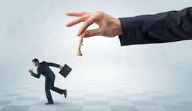 Small businessman running away from big hand with chessman concept stock photography