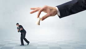 Small businessman running away from big hand with chessman concept. Small frail businessman with suitcase running away from big hand with chessman conceptn royalty free stock photography