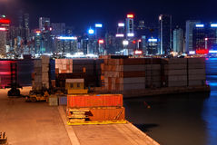 Small freight terminal in Hong Kong at night. Small freight terminal in Kowloon side with view of the skyline of Hong Kong island, at night Stock Photos