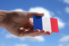 Small French flag. Against sky with cumulus clouds Royalty Free Stock Photos