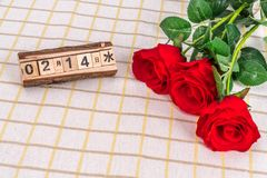 Small fresh rose tablecloth and a desk calendar stock image