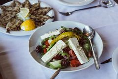 Small fried fish with lemon and Greek salad stock photo