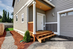 Small front porch with stairs and white entrance door. And gravel walkway to the back yard. Northwest, USA Stock Image