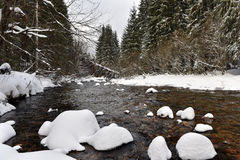 Small frozen river with fresh snow on the rocks Stock Photography