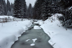 Small frozen river with fresh snow on the rocks Stock Photos