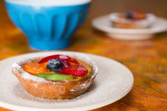 Small fruit tart on a plate. And a cup on background Royalty Free Stock Images